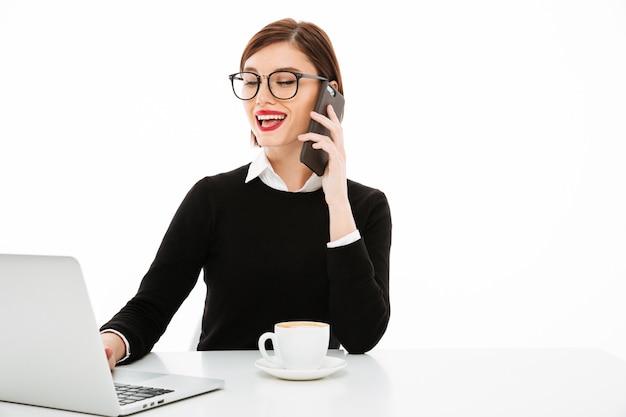 Jonge zakenvrouw met koffie of thee beker en laptop computer, praten via de telefoon
