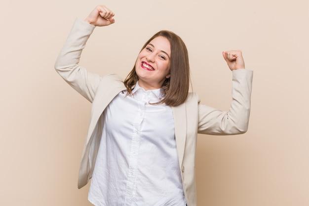 Jonge zakenvrouw met kracht gebaar met armen, symbool van vrouwelijke kracht