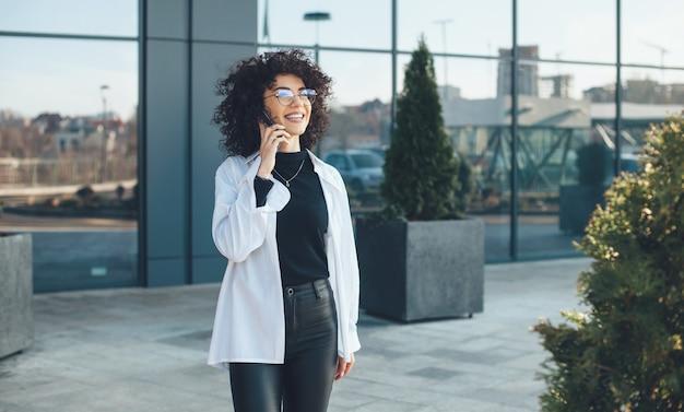 Jonge zakenvrouw met krullend haar en bril poseren buiten tijdens het gesprek aan de telefoon