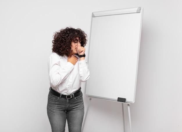 Jonge zakenvrouw met krullend haar en een wit bord