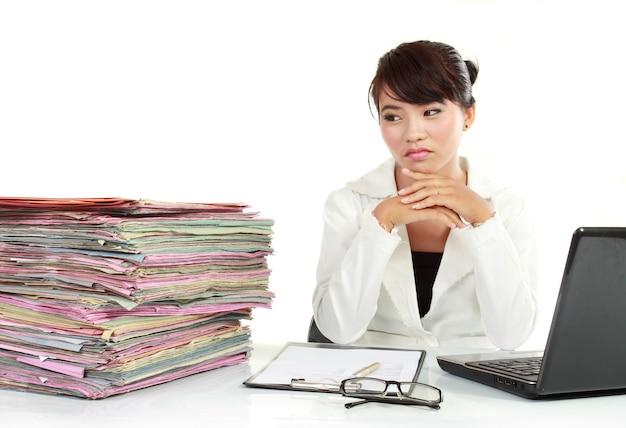 Jonge zakenvrouw met laptop en veel papier