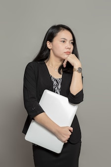 Jonge zakenvrouw met laptop met dromerige uitdrukking