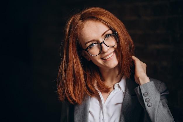 Jonge zakenvrouw met rood haar buitenshuis