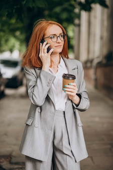 Jonge zakenvrouw met rood haar met behulp van telefoon