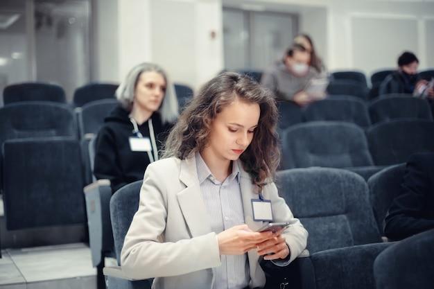 Jonge zakenvrouw met smartphone zittend in collegezaal