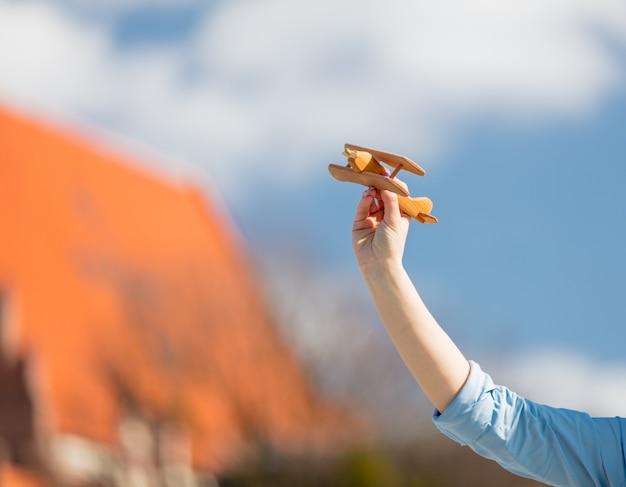 Jonge zakenvrouw met speelgoed houten vliegtuig
