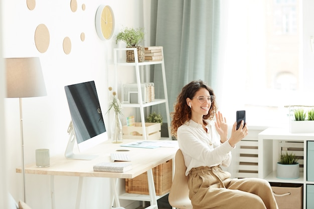 Jonge zakenvrouw met videoconferentie met haar collega's met behulp van smartphone tijdens het verblijf thuis