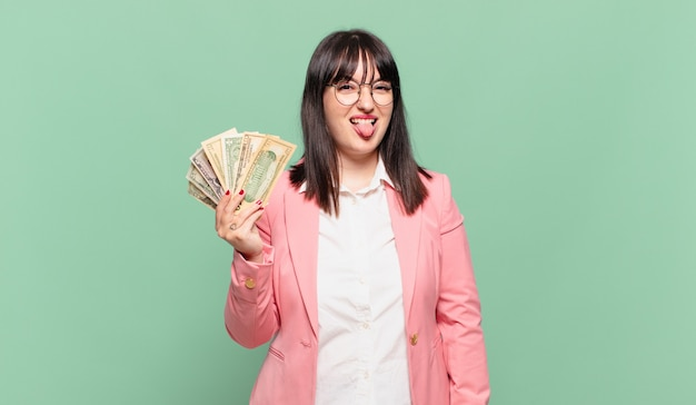 Jonge zakenvrouw met vrolijke, zorgeloze, rebelse houding, grappen maken en tong uitsteken, plezier maken