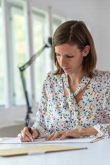 Jonge zakenvrouw of secretaresse zit aan haar bureau en schrijft informatie over papierwerk.