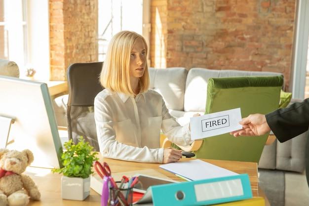 Jonge zakenvrouw ontslagen, kijkt boos. moet haar kantoorspullen inpakken en de werkplek verlaten voor een nieuwe werknemer. problemen in beroep, stress, werkloosheid, nieuwe manier van leven of einde loopbaan.