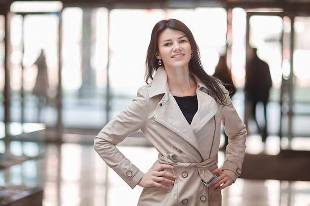 Jonge zakenvrouw op de achtergrond van het kantoor