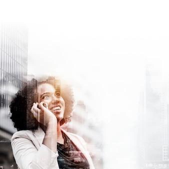 Jonge zakenvrouw op telefoon over stadsachtergrond