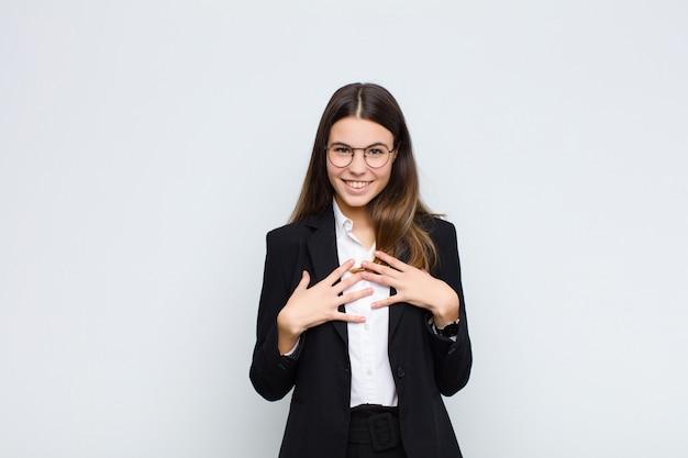 Jonge zakenvrouw op zoek blij, verrast, trots en opgewonden, wijzend naar zichzelf over witte muur