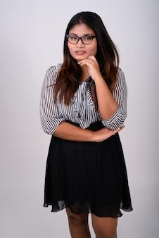 Jonge zakenvrouw permanent en denken terwijl het dragen van een bril