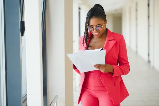 Jonge zakenvrouw permanent in de gang van moderne kantoorgebouw