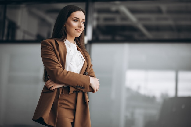 Jonge zakenvrouw permanent in pak in kantoor