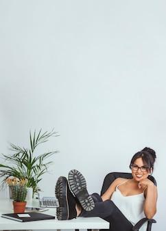 Jonge zakenvrouw poseren met schoenen op de tafel