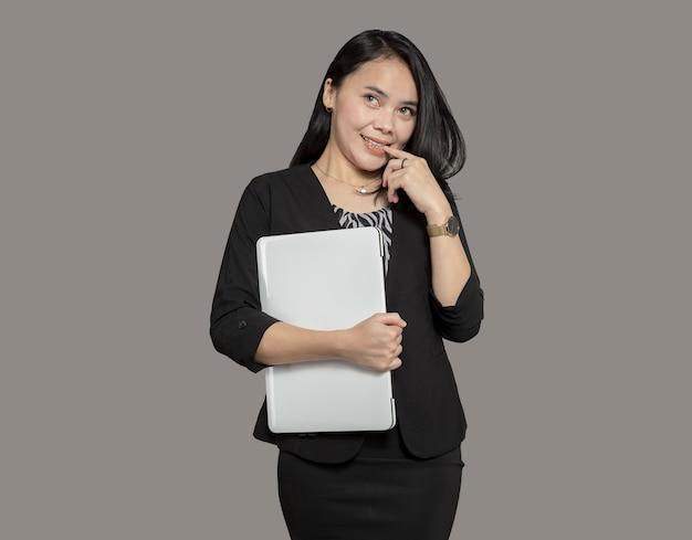 Jonge zakenvrouw poseren terwijl ze een laptop vasthoudt
