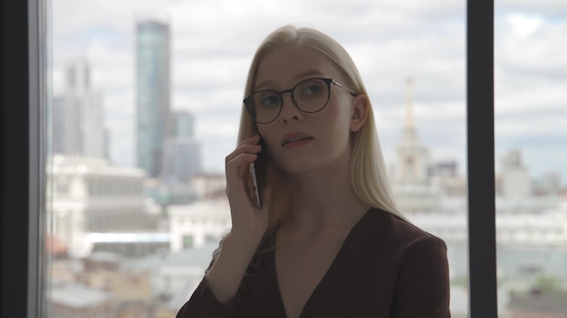Jonge zakenvrouw praten aan de telefoon in de buurt van een groot raam met uitzicht op het stadscentrum. zakenvrouw op kantoor. close-up, 4k uhd.