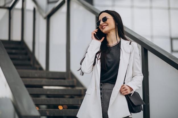 Jonge zakenvrouw praten aan de telefoon in de straat