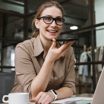 Jonge zakenvrouw praten aan de telefoon tijdens een vergadering