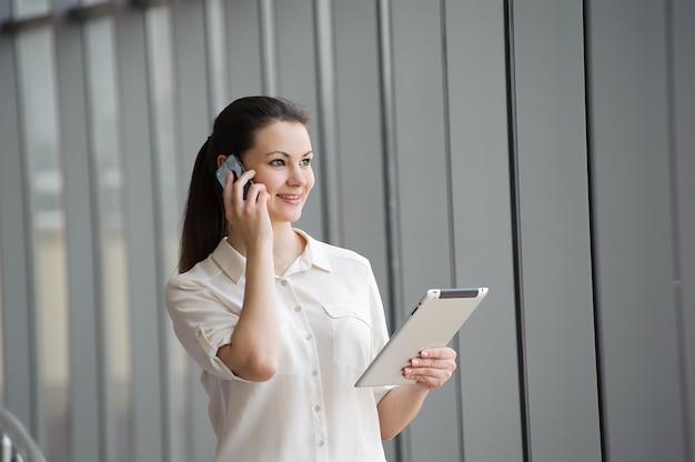 Jonge zakenvrouw praten op mobiele telefoon bij het raam