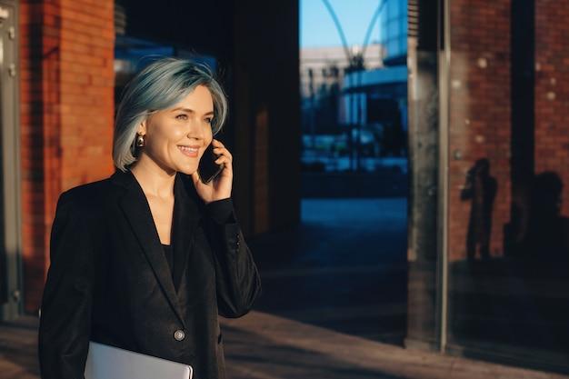 Jonge zakenvrouw praten over telefoon en glimlachen tijdens het wandelen met een computer