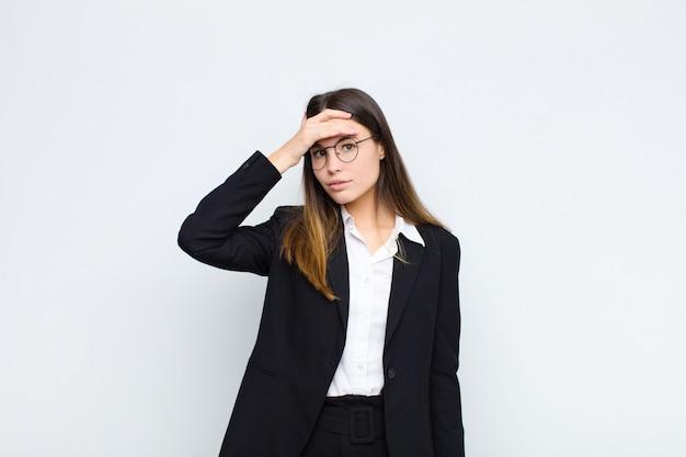 Jonge zakenvrouw raakt in paniek over een vergeten deadline, voelt zich gestrest, moet een puinhoop of fout verbergen tegen een witte muur