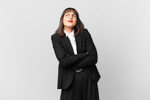 Jonge zakenvrouw schouderophalend, verward en onzeker, twijfelend met gekruiste armen en verbaasde blik