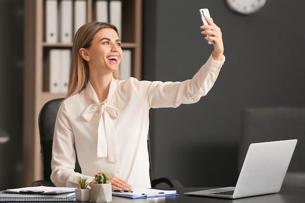 Jonge zakenvrouw selfie te nemen in kantoor