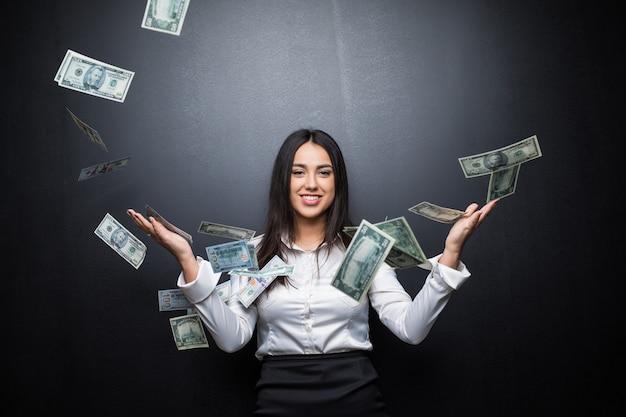 Jonge zakenvrouw staat in de regen van de dollarbiljetten op zwarte muur