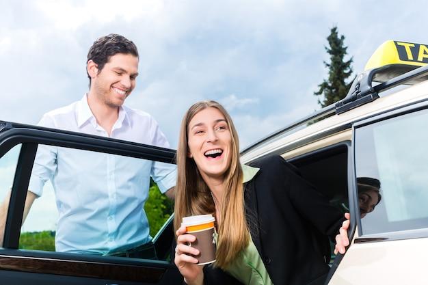 Jonge zakenvrouw stapt uit de taxi, ze houdt een kopje koffie vast
