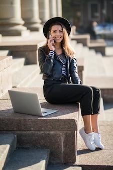 Jonge zakenvrouw student meisje werkt met haar merk laptopcomputer in het stadscentrum
