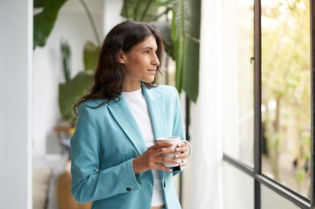 Jonge zakenvrouw tevreden met een goed uitgevoerde klus, ontspannend met haar ochtendkoffie of thee op zoek ...