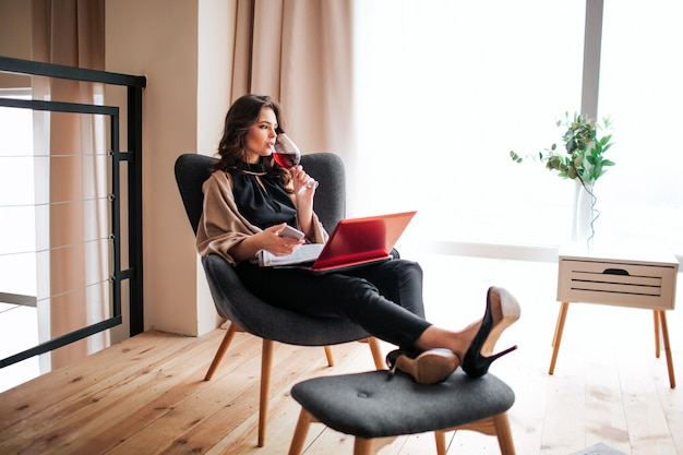 Jonge zakenvrouw thuis werken. drink rode wijn uit glas en kijk naar rechts. houd de telefoon in handen. journal en laptop op poten. afstandswerk. alleen in de kamer. ontspannen.