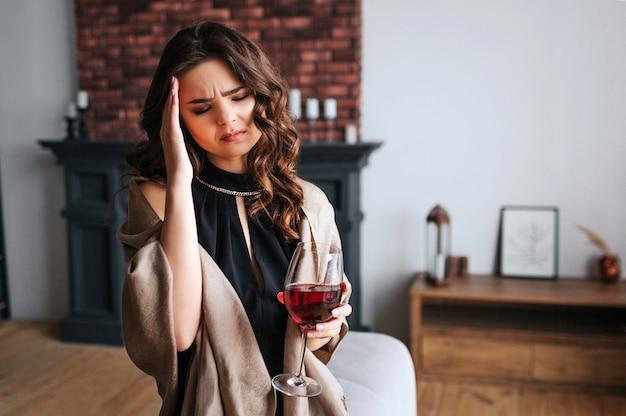 Jonge zakenvrouw thuis werken. ga in de woonkamer staan met een glas rode wijn in de hand. hoofdpijn. alleen. draag een zwarte jurk en een bruine sjaal.