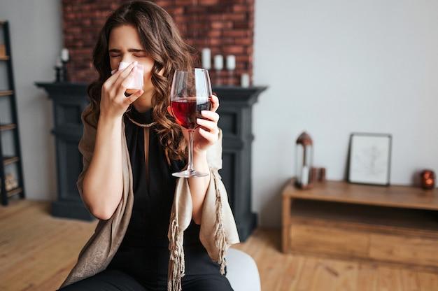 Jonge zakenvrouw thuis werken. het zieke model houdt glas rode wijn in de hand. weefsel neus. zieke zieke vrouw verkouden en virus. ziekte.