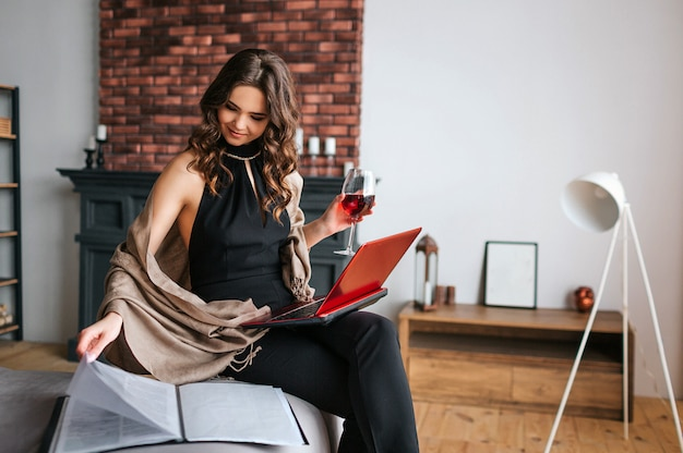 Jonge zakenvrouw thuis werken. modieuze vrouw houd telefoon op knieën en glas rode wijn in de hand. tik op dagboekpagina's. alleen in de woonkamer. draag een zwarte jurk en een bruine sjaal.