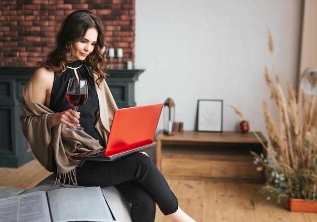 Jonge zakenvrouw thuis werken. zit en houd laptop op knieën. galss rode wijn in rechterhand. drukke aantrekkelijke vrouw op afstand werken. typen op toetsenbord.