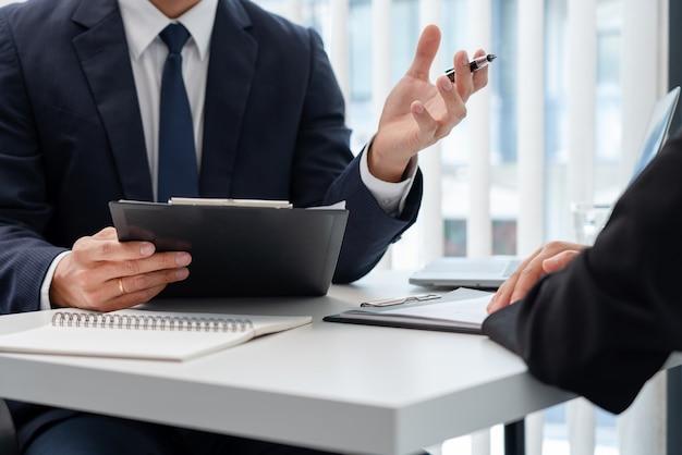 Jonge zakenvrouw uitleggen over haar profiel en cv te houden tijdens zakelijke bijeenkomst