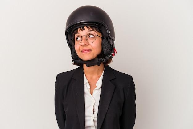 Jonge zakenvrouw van gemengd ras die een geïsoleerde motorhelm draagt en droomt van het bereiken van doelen en doeleinden