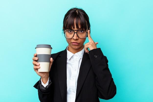 Jonge zakenvrouw van gemengd ras die een koffie vasthoudt op een blauwe achtergrond die naar de tempel wijst met de vinger, denkend, gefocust op een taak.