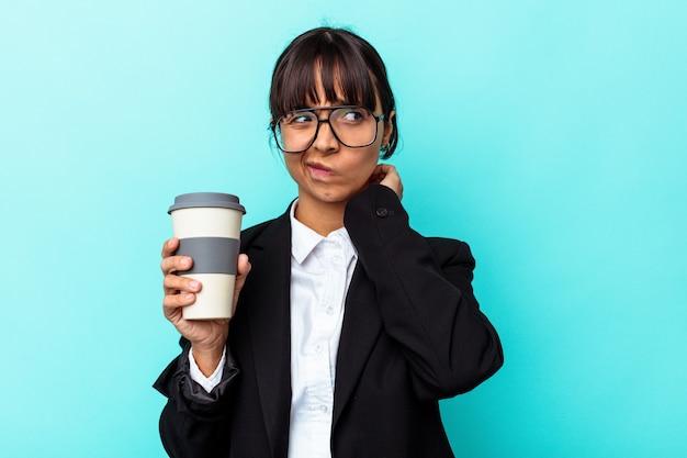 Jonge zakenvrouw van gemengd ras die een kopje koffie vasthoudt op een blauwe achtergrond die de achterkant van het hoofd aanraakt, denkt en een keuze maakt.