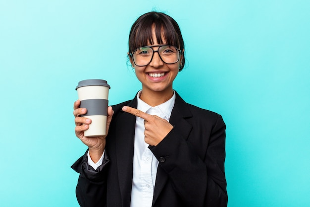 Jonge zakenvrouw van gemengd ras die een kopje koffie vasthoudt op een blauwe achtergrond, glimlachend en opzij wijst, iets op de lege ruimte tonend.
