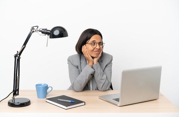 Jonge zakenvrouw van gemengd ras die gefrustreerd op kantoor werkt en oren bedekt