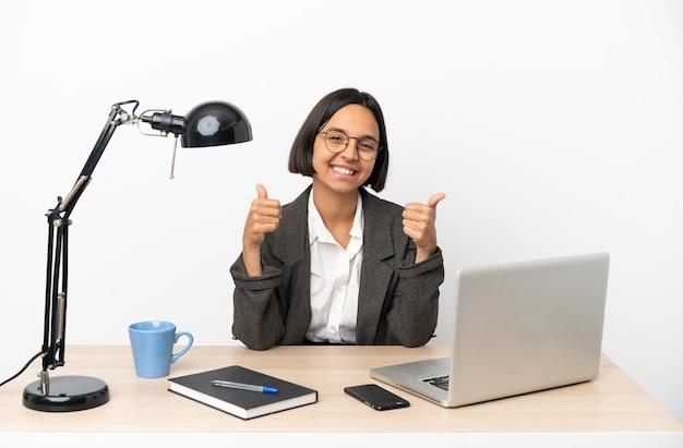 Jonge zakenvrouw van gemengd ras die op kantoor werkt en een duim omhoog gebaar geeft