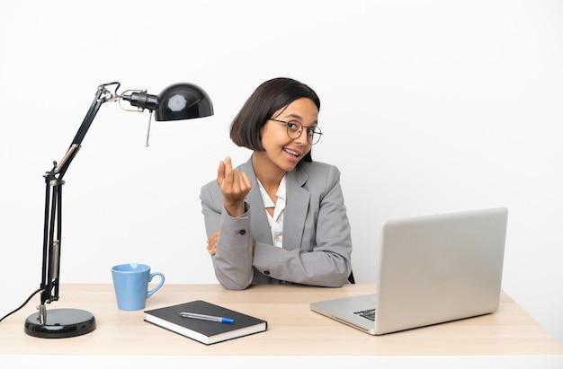 Jonge zakenvrouw van gemengd ras die op kantoor werkt en geldgebaar maakt