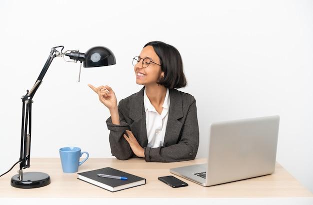 Jonge zakenvrouw van gemengd ras die op kantoor werkt en met de vinger naar de zijkant wijst