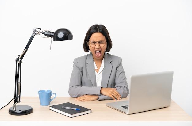 Jonge zakenvrouw van gemengd ras die op kantoor werkt en naar voren schreeuwt met wijd open mond