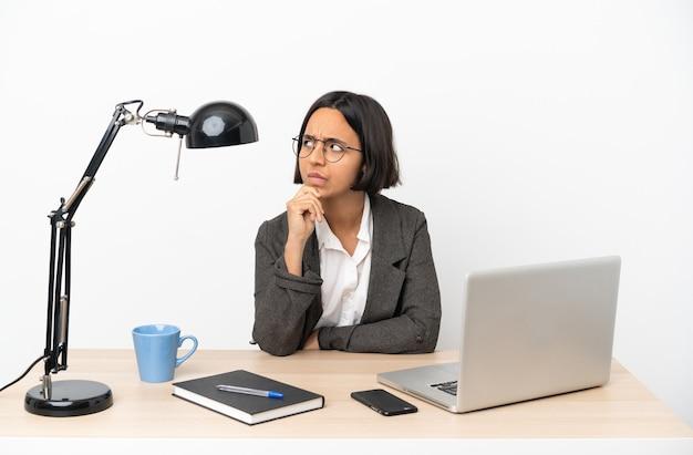 Jonge zakenvrouw van gemengd ras die op kantoor werkt en twijfelt en denkt